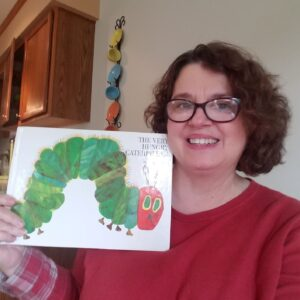 Ms Terri holds up the Very Hungry Caterpillar book