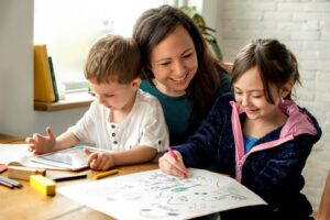 Mom helping two kids with school at home